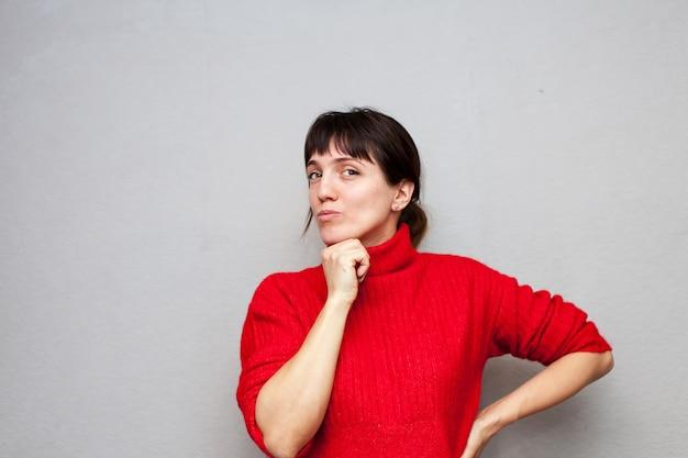 Rozmyślająca kobieta w czerwonym swetrze, trzymając rękę za brodę