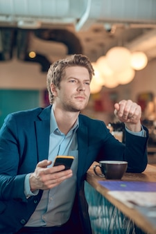 Rozmyślający mężczyzna ze smartfonem i filiżanką kawy