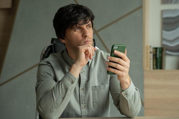 Rozmyślający młody mężczyzna pracujący w nowoczesnym biurze studyjnym osoba korzystająca ze smartfona