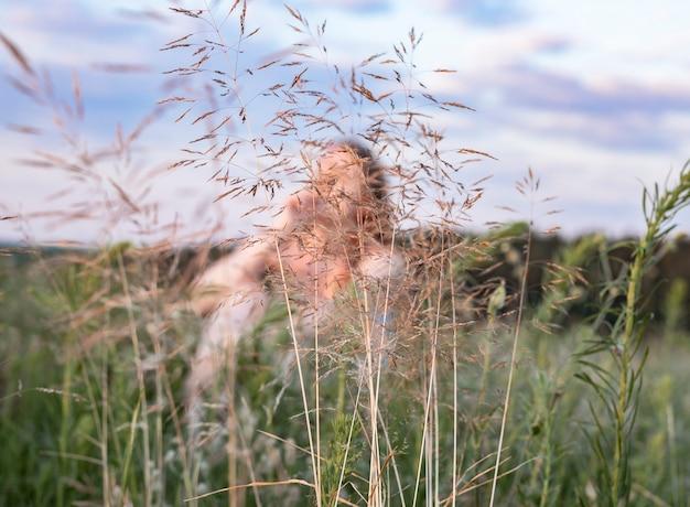 Rozmyta kobieta siedząca na letnim polu z zieloną trawą ciesząca się powolnym życiem w naturze kobieta w ...
