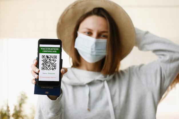 Rozmyta młoda dziewczyna, ubrana w maskę na twarz, trzyma paszport i smartfon z zaświadczeniem o szczepieniu przeciwko chorobie covid-19