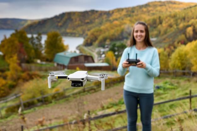 Rozmyta postać dziewczyny steruje dronem na rozmytym tle jesieni. nieostrość consept z górą i jeziorem