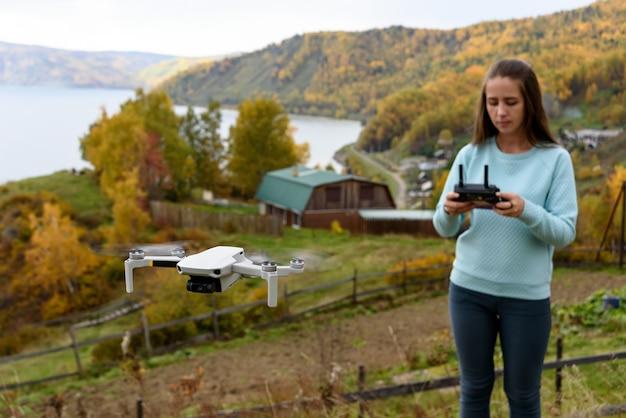 Rozmyta postać dziewczyny steruje dronem na rozmytym tle jesieni. pojęcie nieostrości