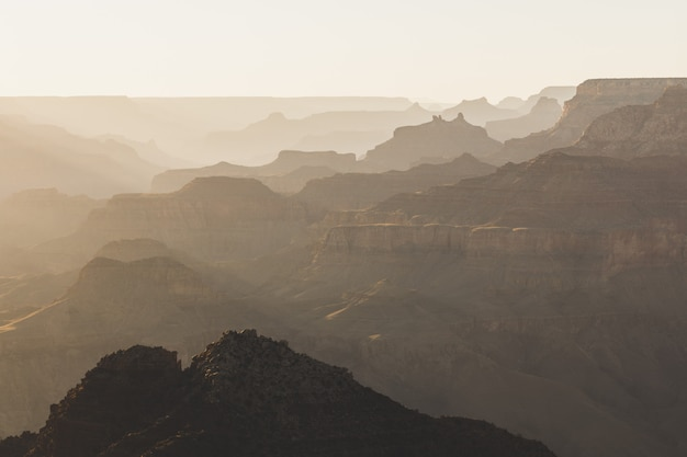 Rozmyte panoramiczne ujęcie wzgórza na tle wysokich gór pokrytych mgłą