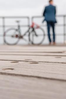 Rozmyty mężczyzna w kostiumie stojący obok roweru