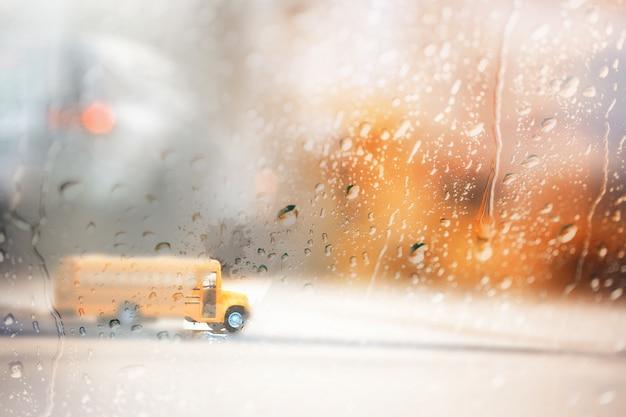 Rozmyty żółty autobus szkolny, widok przez okno w deszczowy dzień.