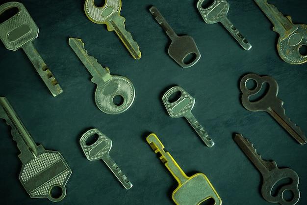 Różna różnorodność starych kluczy uporządkowanych na czarnym drewnianym stole w tle ciemności