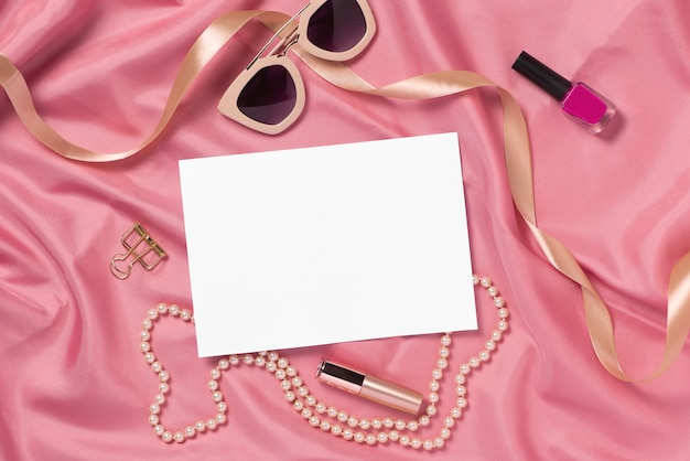 Różne akcesoria damskie na różowej tkaninie. makieta do grafiki. widok z góry.