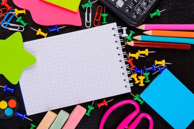 Różne artykuły papiernicze na czarnym stole z miejscem na kopię w notatniku. powrót do koncepcji szkoły