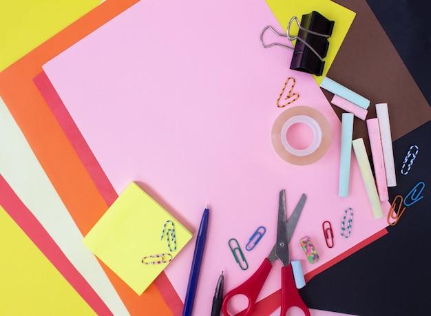 Różne artykuły papiernicze na wielobarwnym kolorowym tle płaskie leżały z miejscem na tekst z powrotem do szkoły