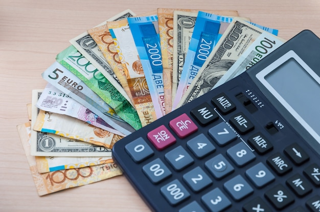 Różne banknoty o różnych nominałach są ułożone w wentylator i kalkulator na stole.