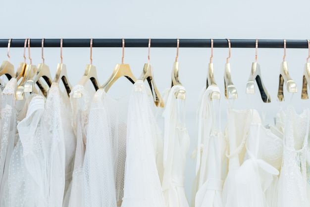 Różne białe sukienki na wieszakach wiszących w rzędzie na stojaku w sklepie z sukniami ślubnymi