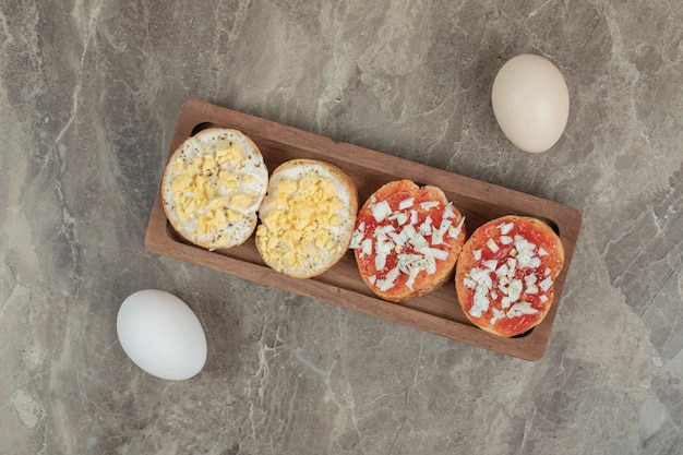 Różne bruschetta na drewnianym talerzu z jajkami. wysokiej jakości zdjęcie
