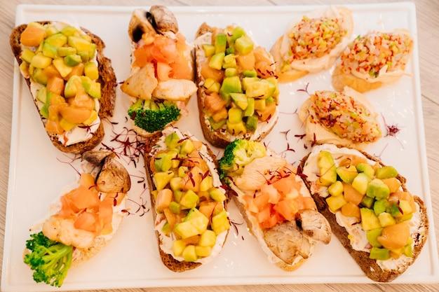 Różne bruschetta z łososiem, awokado, brokułami, mięsem, surówką i serem. przekąski na obiad i bankiet. catering i bufet.