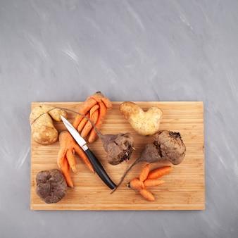 Różne brzydkie warzywa na desce do krojenia koncepcja redukcji odpadów organicznych żywności