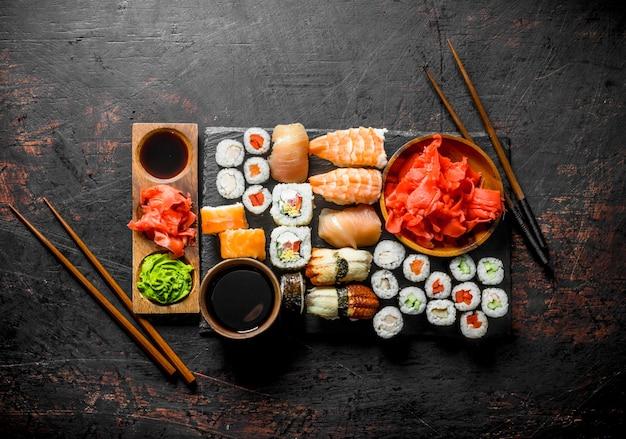Różne bułki, sushi i maki na kamiennej desce z sosem sojowym i imbirem. na ciemnym rustykalnym stole