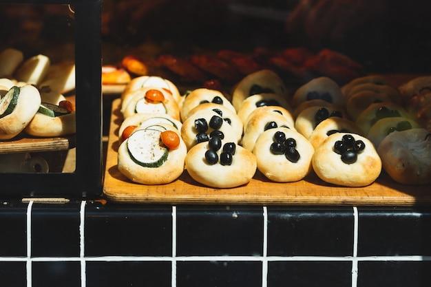 Różne bułki z różnymi nadzieniami w sklepie piekarni