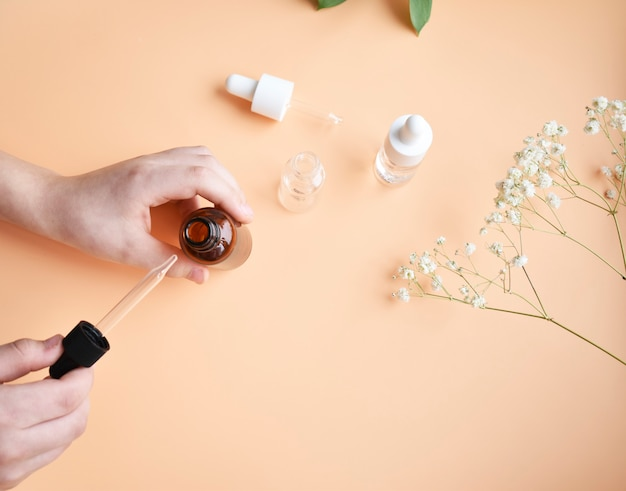 Różne butelki oleju kosmetycznego w kobiecej pipecie. modny produkt kosmetyczny do zabiegów przeciwstarzeniowych.