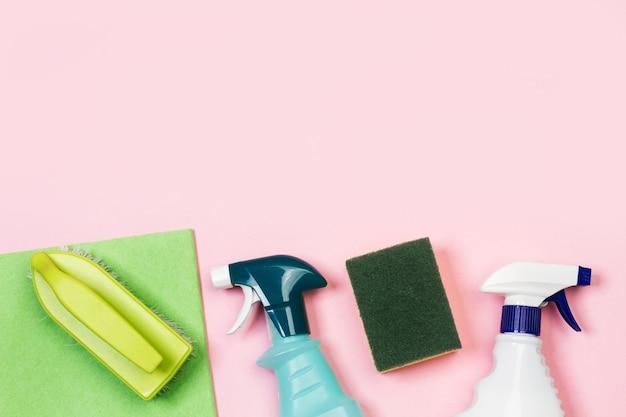 Różne butelki środka czyszczącego na różowym tle