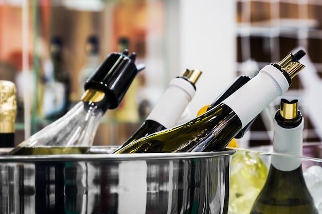 Różne butelki wina i szampana w wiadrze z lodem podczas degustacji
