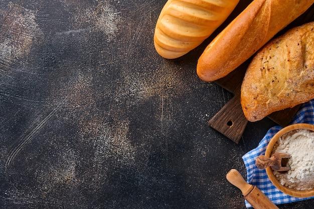 Różne chrupiące pieczywo i bułeczki, mąka pszenna i kłosy na brązowym starym stole betonowym