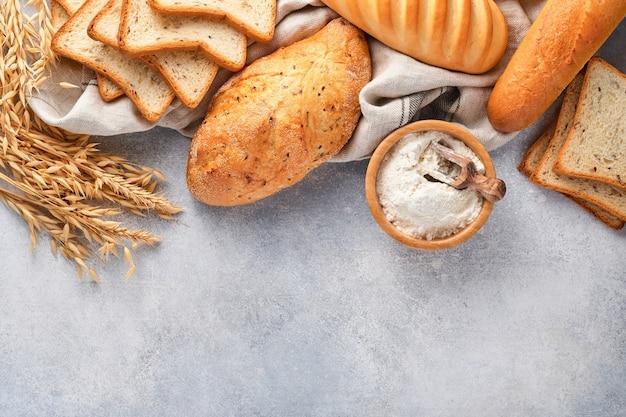 Różne chrupiące pieczywo i bułeczki, mąka pszenna i kłosy na jasnoszarym betonowym tle.