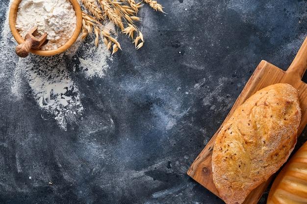 Różne chrupiące pieczywo i bułeczki, mąka pszenna i kłosy na szarym starym stole betonowym.