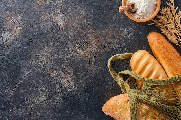 Różne chrupiące pieczywo i bułeczki w siatkowych torebkach lub torbie na zakupy, mąka pszenna i kłosy na brązowym starym stole betonowym
