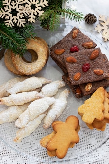 Różne ciasteczka, gałązki jodły i girlanda na jasnym tle. styl rustykalny, selektywne skupienie.