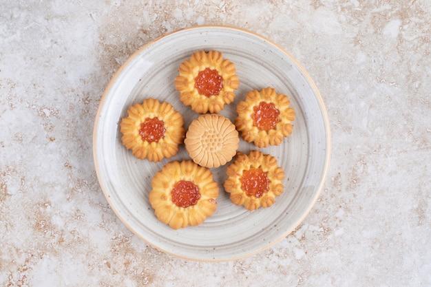 Różne ciasteczka na talerzu, na marmurze.