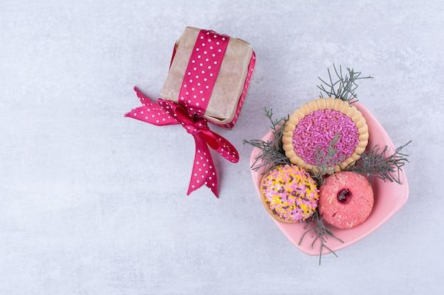 Różne ciasteczka ozdobione spryskiwaczami i pudełkiem prezentowym.