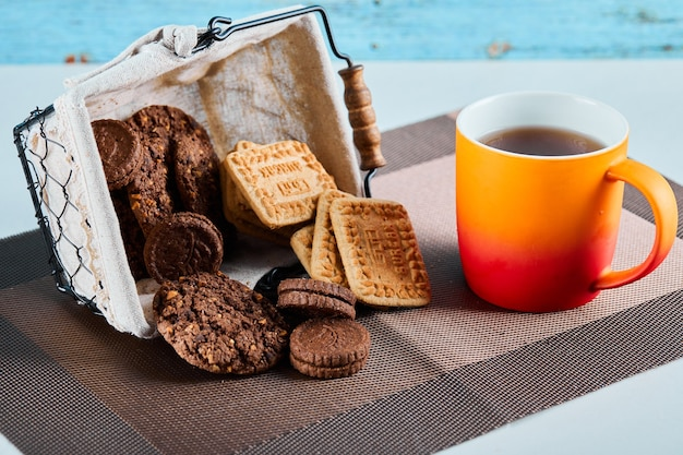 Różne ciastka, cukierki i filiżanka herbaty na szarej powierzchni.