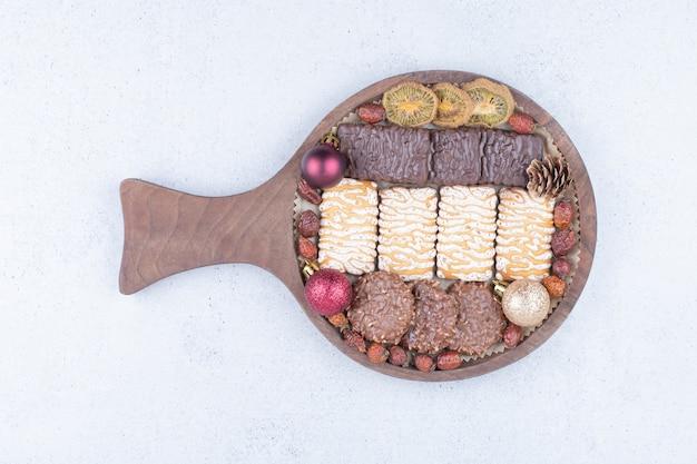 Różne ciastka, suszone owoce i bombki na desce.