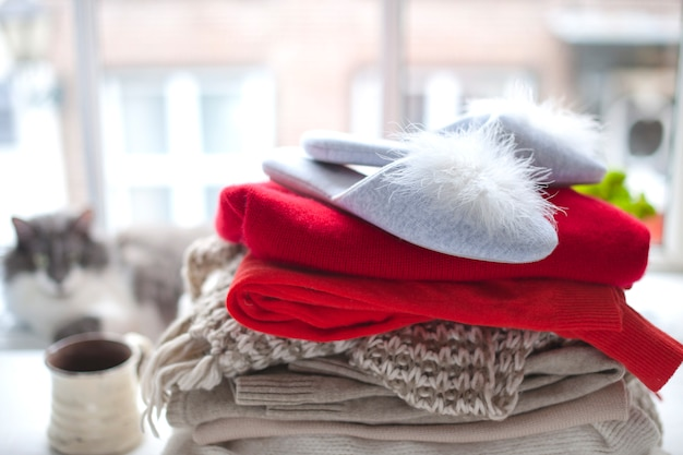 Różne ciepłe ubrania i kapcie przy oknie i kot. swetry na jesień i zimę. herbata i wolne miejsce na tekst.