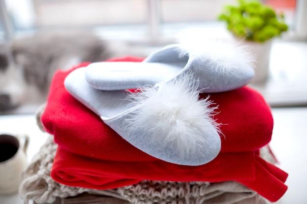 Różne ciepłe ubrania i kapcie przy oknie. swetry na jesień i zimę. wolne miejsce na tekst.