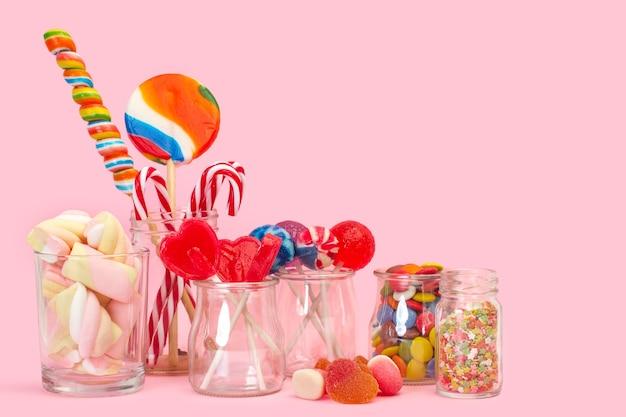 Różne cukierki i lizaki w kryształowych słoikach na różowym tle