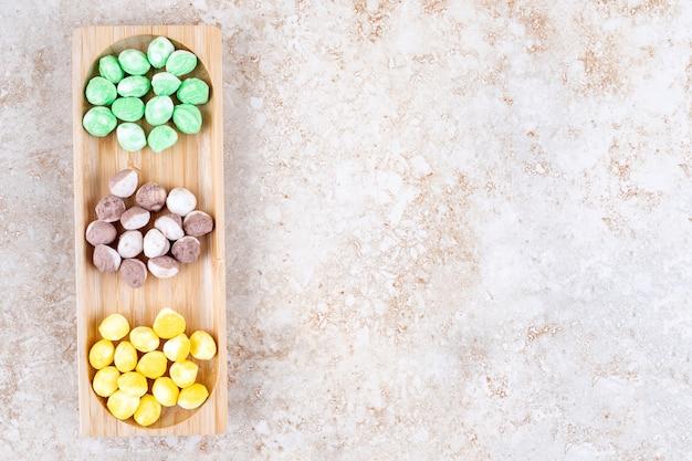 Różne cukierki w małej drewnianej tacy