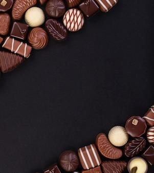 Różne cukierki z białej i ciemnej czekolady na czarnym stole