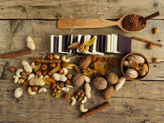 Różne czekoladki, orzechy i inne słodycze na drewnianym stole