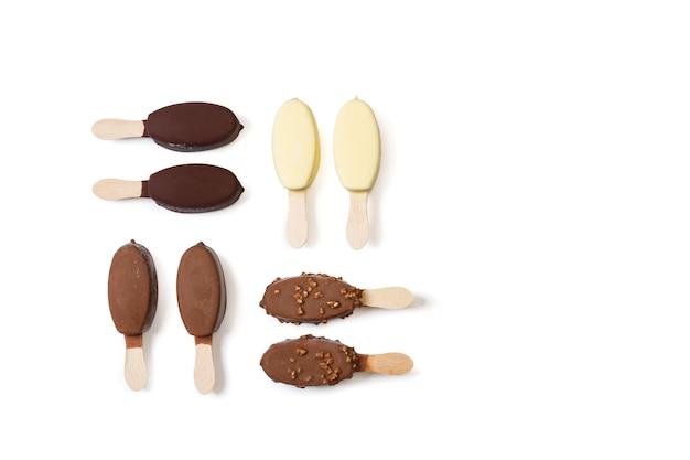 Różne czekoladowe lizaki dipped ice na białym tle w widoku z góry