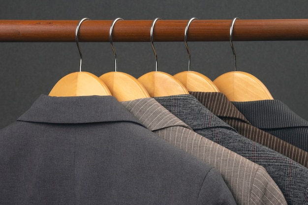 Różne damskie klasyczne kurtki biurowe wiszą na wieszaku do przechowywania ubrań