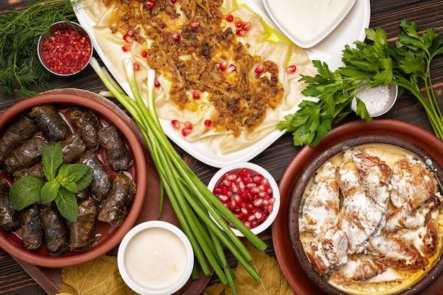 Różne dania orientalne, dolma, kurczak z sosem chkmeruli, pilaw, z sosem i ziołami, na drewnianej desce