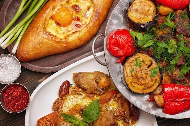Różne dania orientalne, saj, pilaw i chaczapuri z przyprawami i ziołami