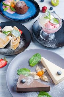 Różne desery: czekoladowe fondue, lody, strudel jabłkowy, sernik