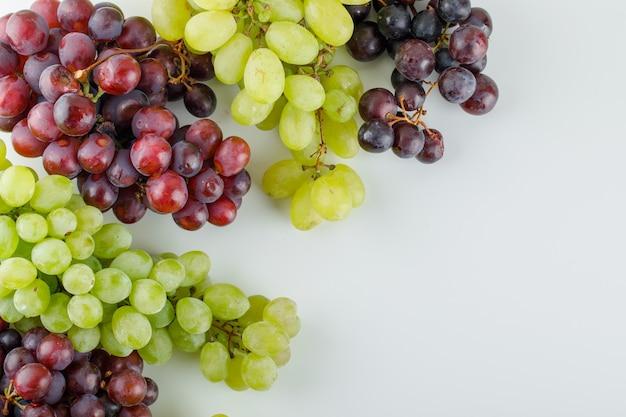 Różne dojrzałe winogrona leżały płasko na białym