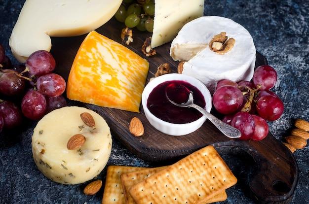 Różne domowe kawałki sera z dżemem, winogronami, ciasteczkami i orzechami, ciasteczkami i orzechami na stole. świeży produkt mleczny, przekąska serowa, zdrowa żywność ekologiczna. pyszna przystawka.