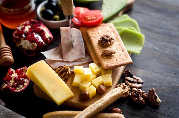 Różne domowe kawałki sera z miodem, owocami, ciasteczkami i orzechami na stole. świeży produkt mleczny, zdrowa żywność ekologiczna. pyszna przystawka.