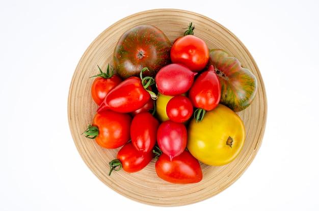 Różne domowe kolorowe pomidory różne kształty na drewnianym talerzu. zdjęcie studyjne.