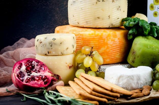 Różne domowe serowe różnego rodzaju z warzywami, owocami, ciasteczkami i orzechami na stole. świeży produkt mleczny, zdrowa żywność ekologiczna. pyszna przystawka.