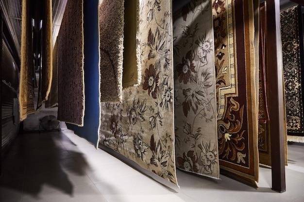 Różne dywany wiszące na stojakach. profesjonalne czyszczenie i suszenie dywanów
